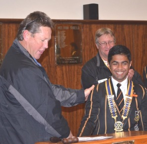 From left, Marc Bradley of the Queenstown Rotary Club inducts Queen's College Interact president Kiran Jomon into the position while Keith Wood applauds at the back